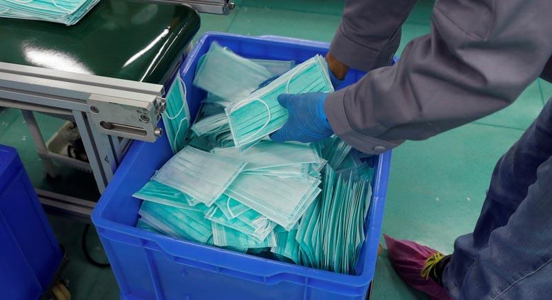 Man loads face masks into a bin