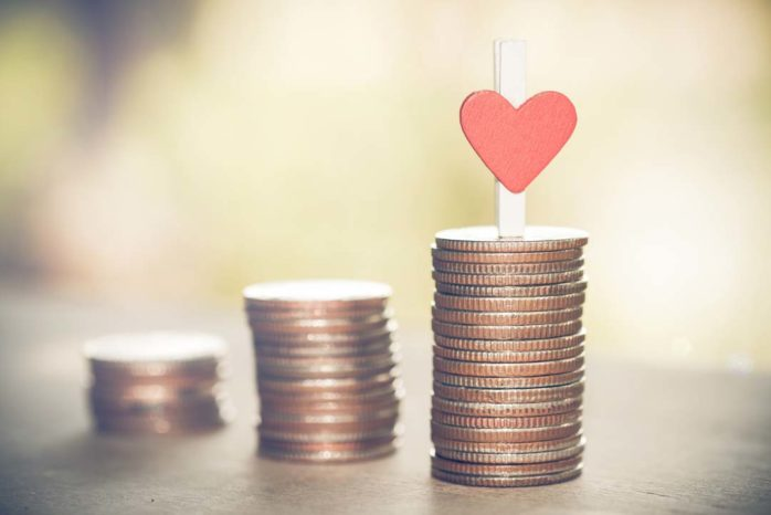 Heart on coins tower with nature background. business and saving